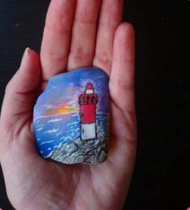 phare et océan avec coucher de soleil, peints au Posca sur un galet